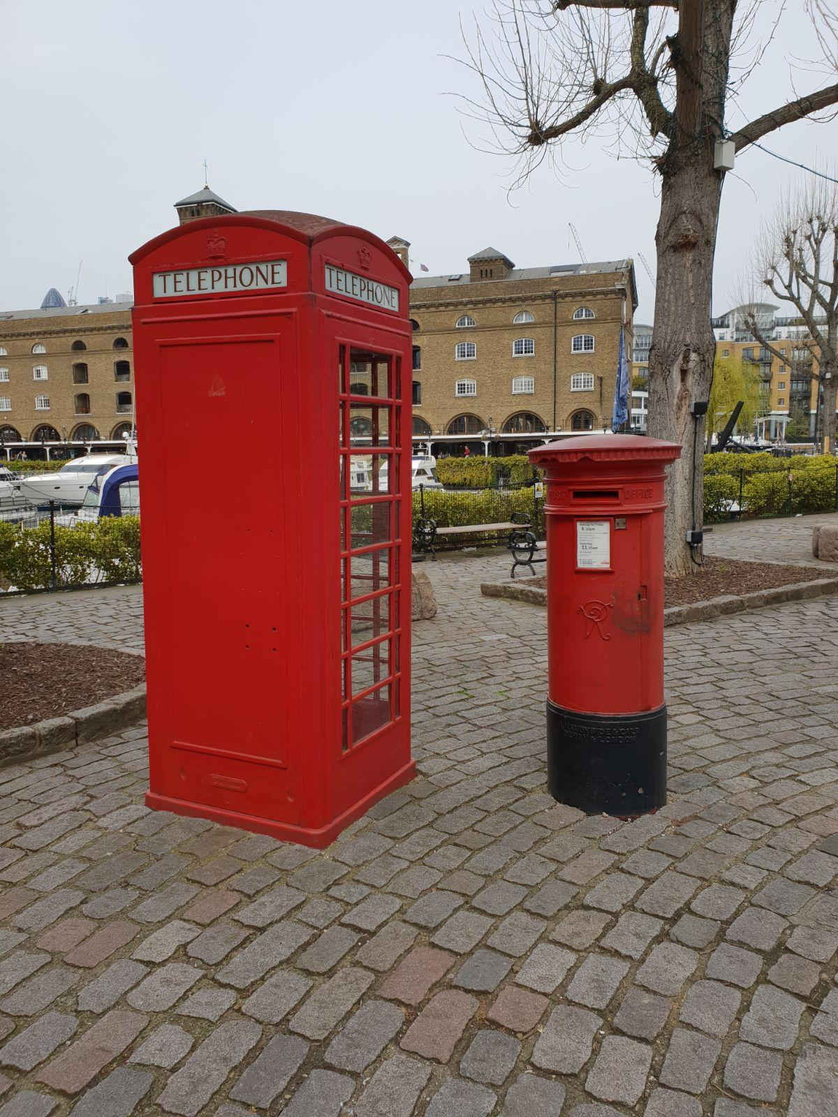 A photograph of a red telephone box beside a red post box