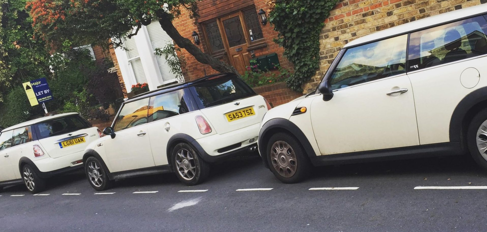 Three cream Mini Coopers in a row